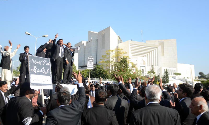 Lawyers of bar associations of five divisions chant slogans during a sit-in at Constitutional Avenue in front of Supreme Court building, demanding set up LHC benches in five divisions.— Photo by INP