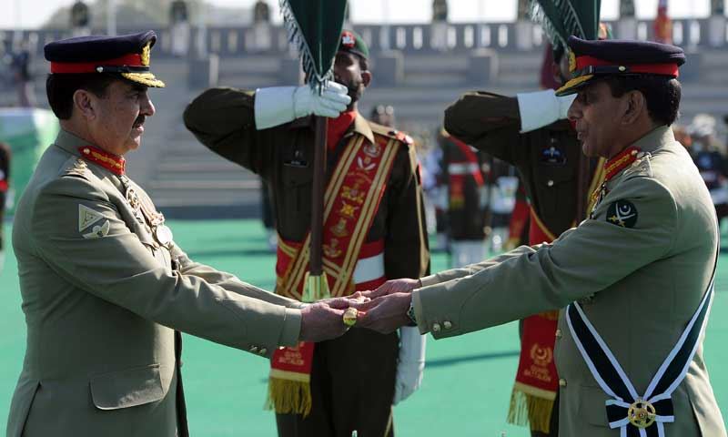 Outgoing army chief Ashfaq Kayani (R) presents the change of command baton to newly-appointed army chief General Raheel Sharif during the change of command ceremony in Rawalpindi on Nov 29, 2013. — Photo by AFP
