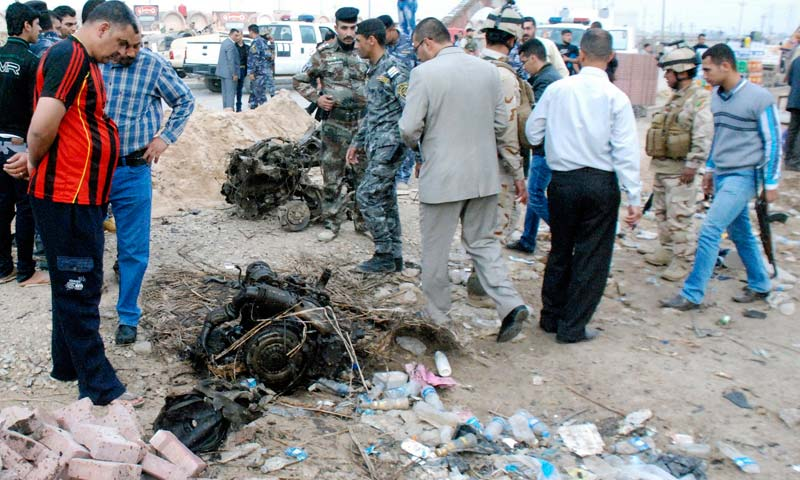 Iraqi security forces inspect the site of a car bomb attack in Kut, 150 km southeast of Baghdad. -Reuters Photo