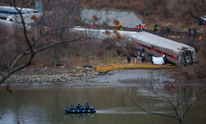 Viewed from Manhattan, first responders and others work at the scene of a derailed Metro North passenger train in the Bronx borough of New York Dec 1, 2013. – AP Photo
