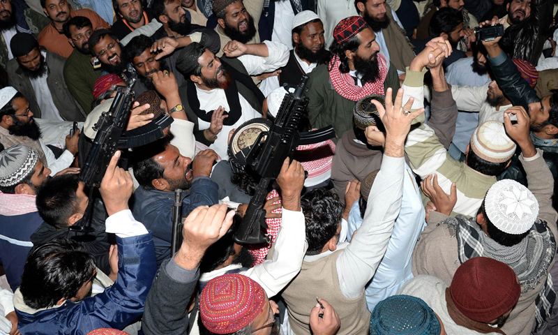 Protesters, some brandishing guns, gathered outside a hospital following the killing of Maulana Shamsur Rehman Muavia, chief of the ASWJ for Punjab province, in Lahore on Dec 6, 2013.— AFP Photo