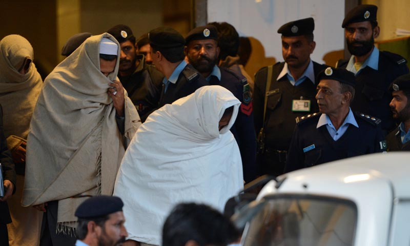 Pakistani policemen escort newly-identified missing persons following an identification process as they leave the Supreme Court building in Islamabad on December 7, 2013.  — Photo by AFP