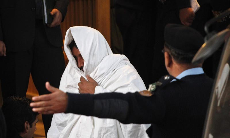 Police officers escort a man, who covers himself with a cloth, as he leaves after appearing before the Supreme Court in Islamabad December 7, 2013. — Photo by Reuters