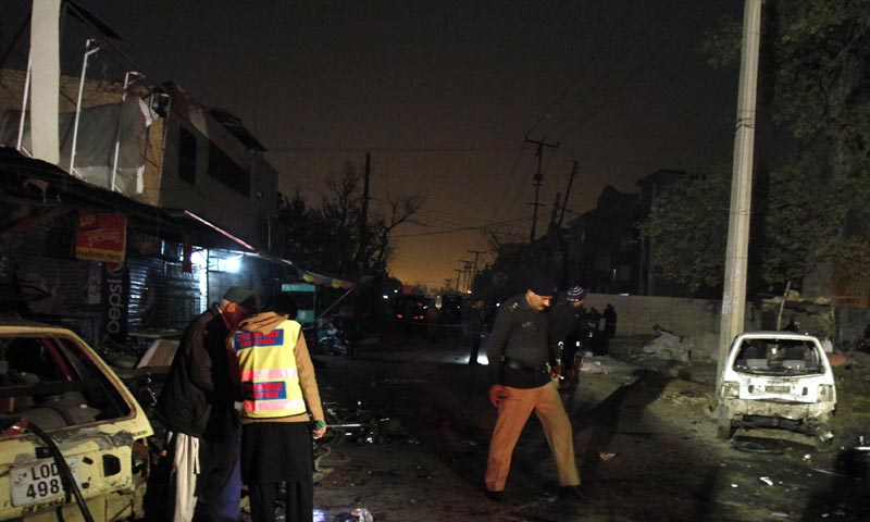 A police officer and a rescue worker examine the site of a suicide bombing  in Rawalpindi. -AP Photo