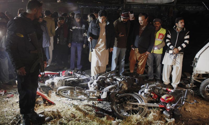 Police officers examine damaged motorcycles at the site of a suicide bombing that killed several people and wounded others in Rawalpindi. -AP Photo