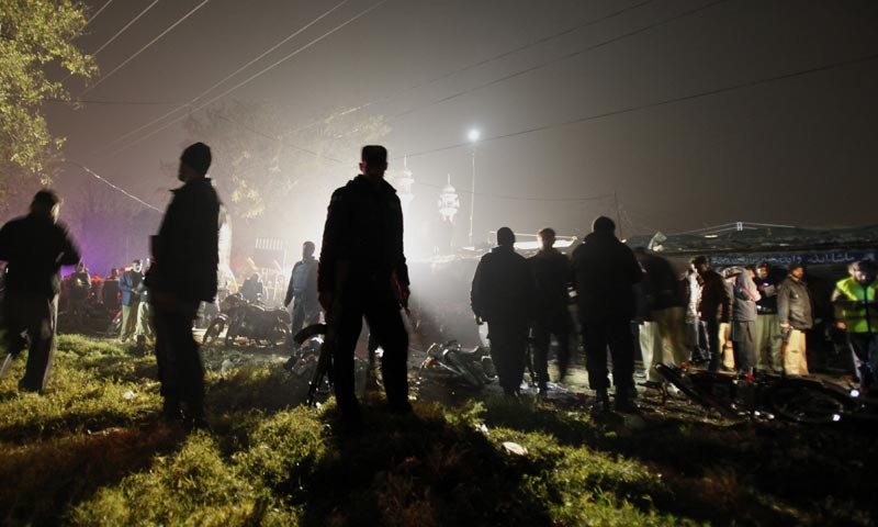Police commandos secure an area while security officials examine the site of a suicide bombing in Rawalpindi. -AP Photo