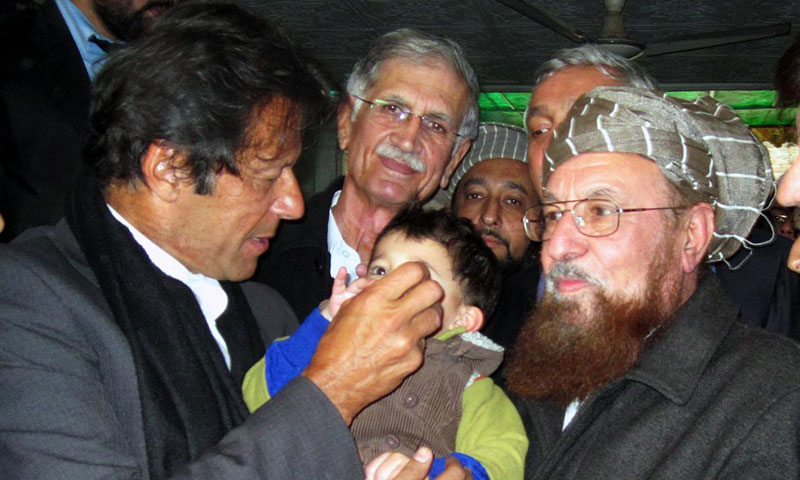 PTI chief Imran Khan administering anti polio drops to grandson of Maulana Samiul Haq at Darul Aloom Haqqania on Wednesday. – Photo by Online