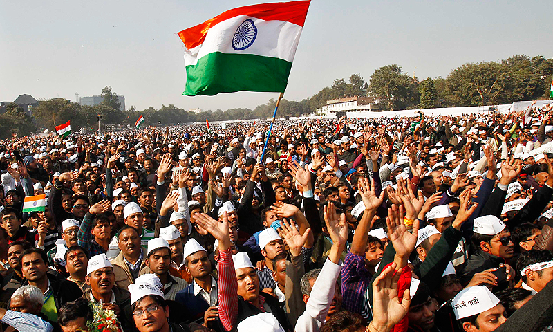 Supporters of the Aam Aadmi Party (AAP) wave as they listen to a speech by their leader Arvind Kejriwal after he took an oath as the new chief minister of Delhi during a swearing-in ceremony. -Photo by Reuters