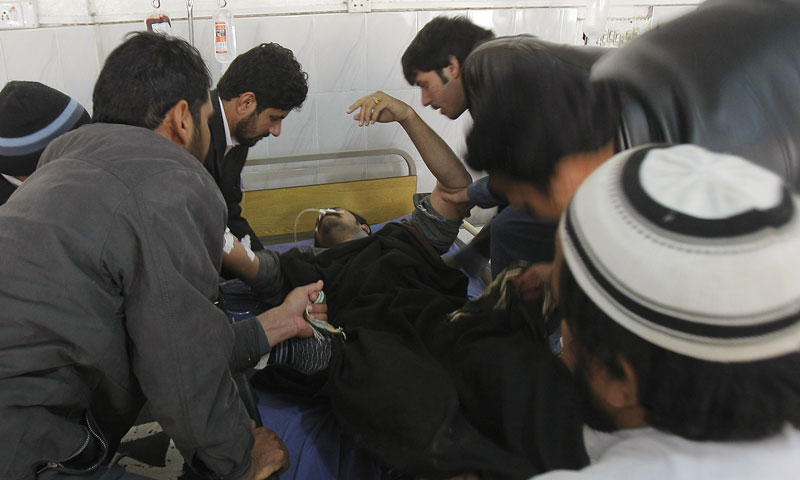 Hospital staff members help an injured health move to another room at a local hospital in Peshawar, Saturday, Dec 28, 2013. — Photo by AP