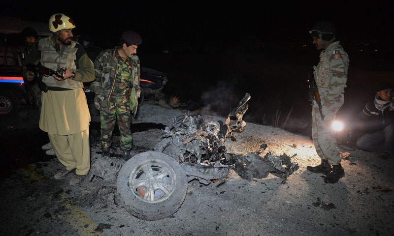 Security personnel look at the wreckage of a car used in Wednesday's suicide bombing. — Photo by AFP