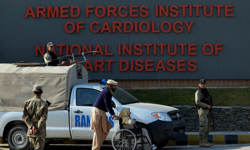 Pakistani rangers and army soldiers stand guard as a patient is wheeled in front of the Armed Forces Institute of Cardiology in Rawalpindi on Jan 3, 2014, where former military ruler Pervez Musharraf is being treated. — Photo by AFP