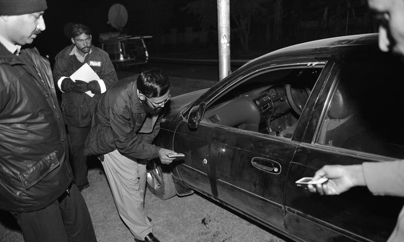 A Pakistani mourner (2R), along with investigators, inspects a car after an attack on ASWJ leader in Islamabad on January 3, 2013. – AFP