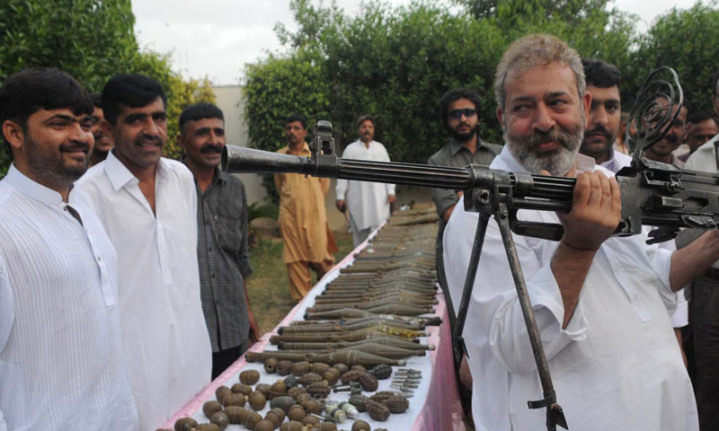 In this picture taken on May 11, 2012, Pakistan's senior police investigator Chaudary Aslam holds a machine gun recovered from militants with other ammunition in Karachi. — Photo by AP
