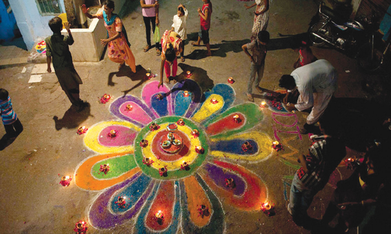 Members of the Pakistani Hindu community make a rangoli during Diwali celebrations in Karachi. 	— Reuters