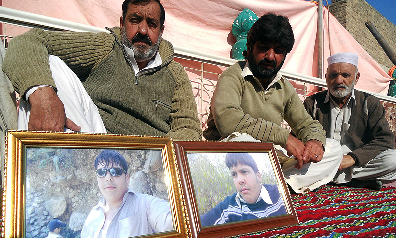 Mujahid Ali (L), father of Pakistani student Aitzaz Hassan, who was killed in a suicide attack outside his school, sits with mourners beside the photographs of his son in Hangu district. -Photo by AFP