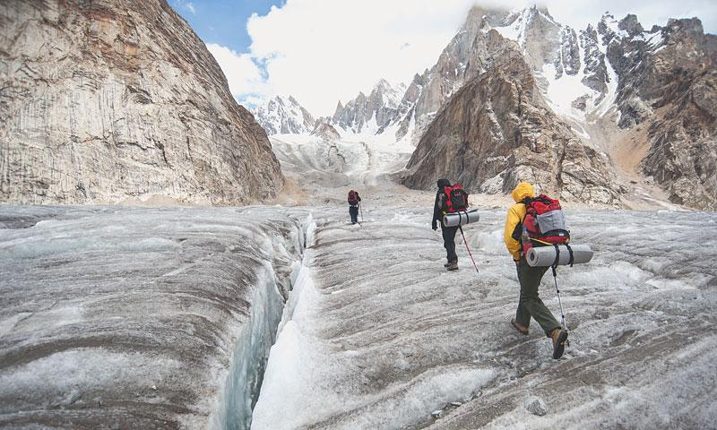 Walk the line: mountaineers and porters trekking across a glacier. - Photo by Nadir Toosy