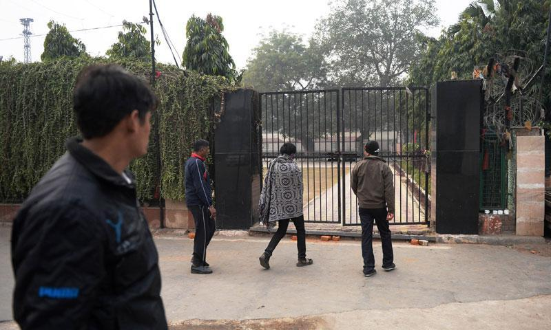 Unidentified passersby walk near a gate to the yard of the SE Road Railway Officers Club on January 15, 2013, where a Danish tourist visiting India was allegedly raped in New Delhi on January 14. — Photo by AFP