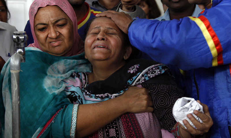 People comfort a woman whose son who was killed by unknown gunmen in Karachi, Pakistan, Tuesday, Jan 21, 2014. — Photo by AP