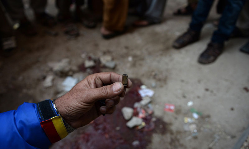 A volunteer holds up an empty bullet casing at the site of a gunmen attack on health workers in Karachi on Jan 21, 2014. — Photo by AFP