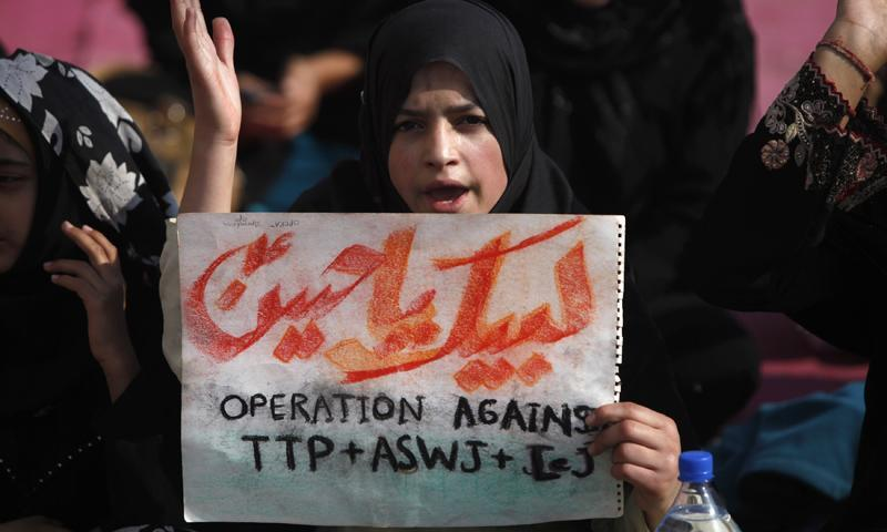 A Shia Muslim girl holds a placard as she chants slogans during a protest, to condemn the killings of Tuesday night's bomb attack on a bus, in Karachi January 23, 2014. – Reuters Photo