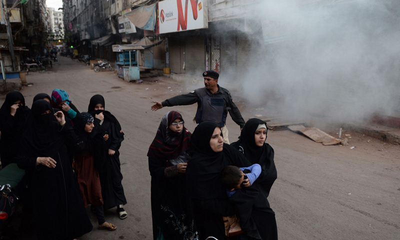 Shia Muslims react after police fired teargas during a protest against the killing of Shia Hazara community members in Karachi on January 23, 2014.  – AFP Photo