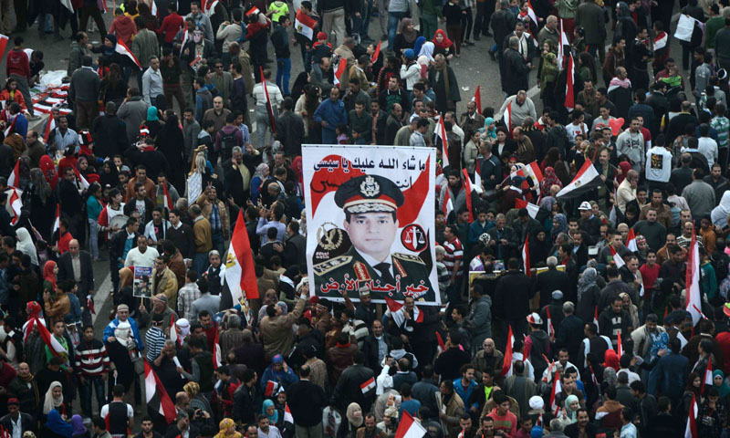 Egyptians wave the national flag and hold up pictures of Defence Minister army chief Abdel Fattah al-Sisi in Cairo's Tahrir Square on January 25, 2014. – AFP
