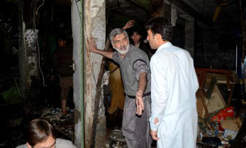 People inspect site of the suicide bombing in Peshawar on Tuesday night. – Photo by Zahir Shah Sherazi
