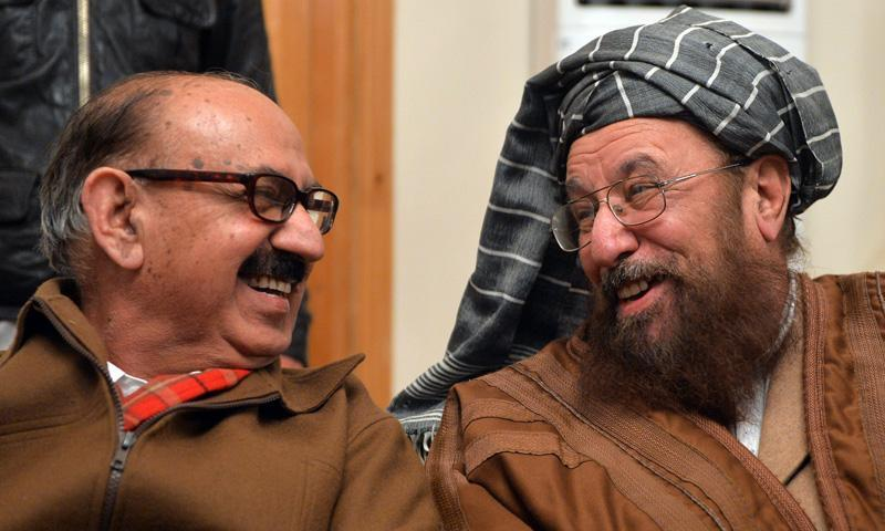 Tehreek-e-Taliban Pakistan committee member Maulana Samiul Haq and Irfan Siddiqui smile as they interact prior to a joint press conference following their meeting in Islamabad on February 6, 2014. – AFP Photo