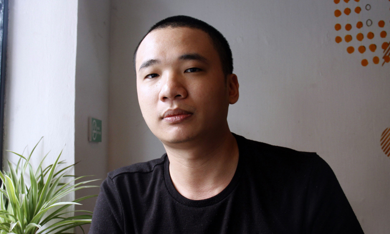 """This picture taken on February 5, 2014 shows Nguyen Ha Dong, the author of the game Flappy Bird relaxing inside a coffee shop in Hanoi.  The Vietnamese developer behind the smash-hit free game Flappy Bird has pulled his creation from online stores after announcing that its runaway success had ruined his """"simple life"""". — AFP Photo"""