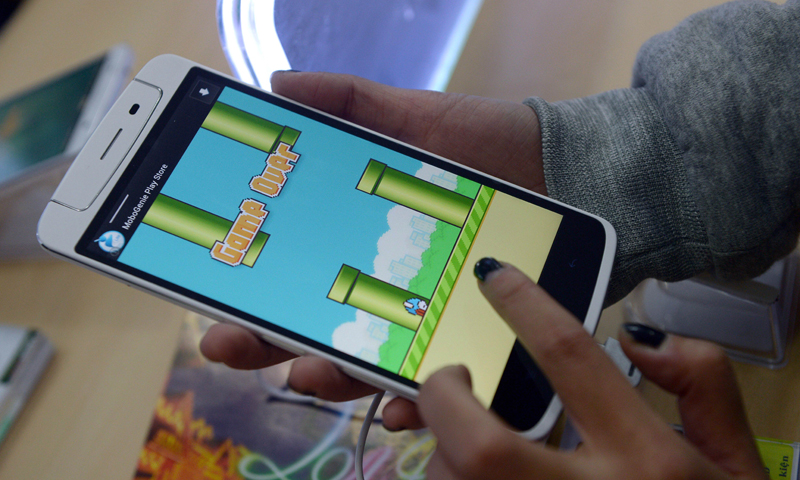 """An employee plays the game Flappy Bird at a smartphone store in Hanoi on February 10, 2014.  The Vietnamese developer behind the smash-hit free game Flappy Bird has pulled his creation from online stores after announcing that its runaway success had ruined his """"simple life"""". — AFP Photo"""