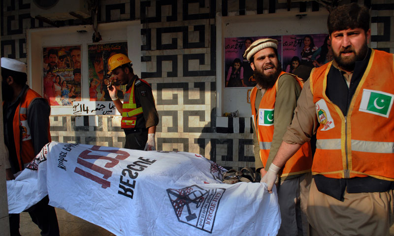Rescue workers remove a  body from the site of a grenade attack Shama movie theater in Peshawar, Pakistan, Tuesday, Feb 11, 2014. — Photo by AP