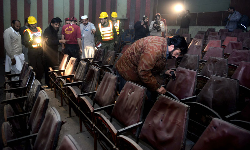 Volunteers search a cinema hall after a grenade attack in Peshawar on February 11, 2014. — Photo by AFP