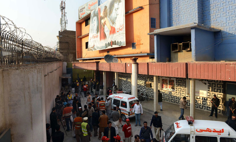 Security officials and volunteers gather outside the Shama cinema after a grenade attack in Peshawar on February 11, 2014. — Photo by AFP