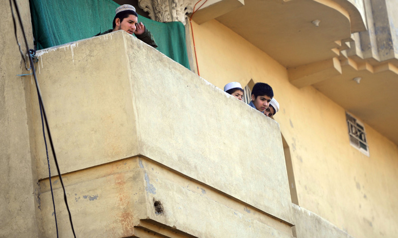 Pakistani children stand on a balcony at the house of anti-drone campaigner Kareem Khan in Rawalpindi on February 11, 2014. – AFP