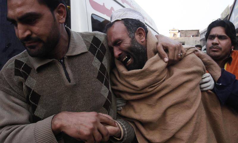 A relative comforts a man grieving over the death of his brother, killed in a grenade attack, at the Lady Reading Hospital in Peshawar February 11, 2014. – Reuters Photo