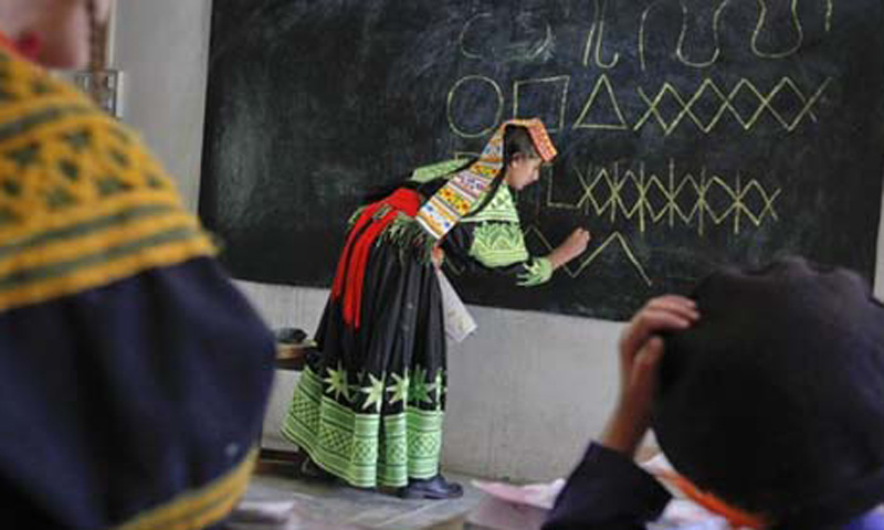 A Kalash school teacher  writes letters from the Kalasha alphabet on a blackboard during a lesson at the Kalasha Dur school and community centre in Brun village, located in Bumboret Kalash valley. — Reuters/File Photo