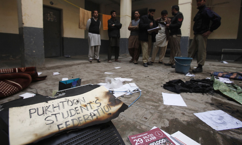 Police collect evidence and speak to witnesses at a hostel after it was burnt during a clash at the University of Peshawar on Feb 14, 2014. — Reuters