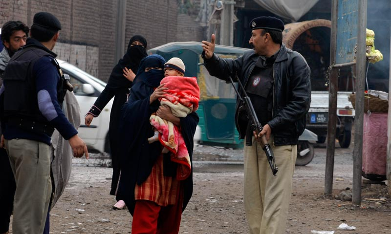In this Feb. 2, 2014 photo, Pakistani police officer stand guard as people who need to vaccinate their children against polio approach health workers, in Peshawar, Pakistan. —AP Photo