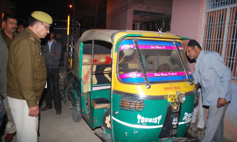 Indian policemen investigate an auto rickshaw of  Bunty Sharma, 32, outside his house, in Agra, India. — Photo by AP
