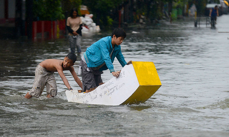 "Children use a makeshift ""boat"" to cross a flooded street in Manila on August 19, 2013 as heavy rains hit the Philippine capital. Heavy rain forced all schools, government offices and the stock exchange to close on August 19, as waist-deep water flooded parts of the city.   AFP PHOTO / NOEL CELIS"