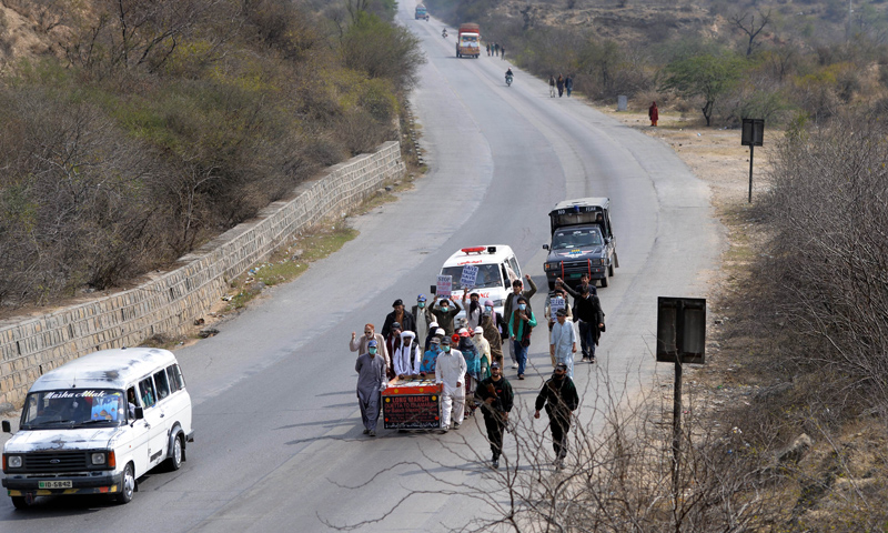 In this photograph taken on February 24, 2014 a group of Baloch people, led by Mama (uncle) Qadeer push a hand cart carrying the pictures of their missing loved ones as they walk along the Grand Trunk Road in the town of Dina, some 100 kilometers south of Islamabad.  — Photo by AFP