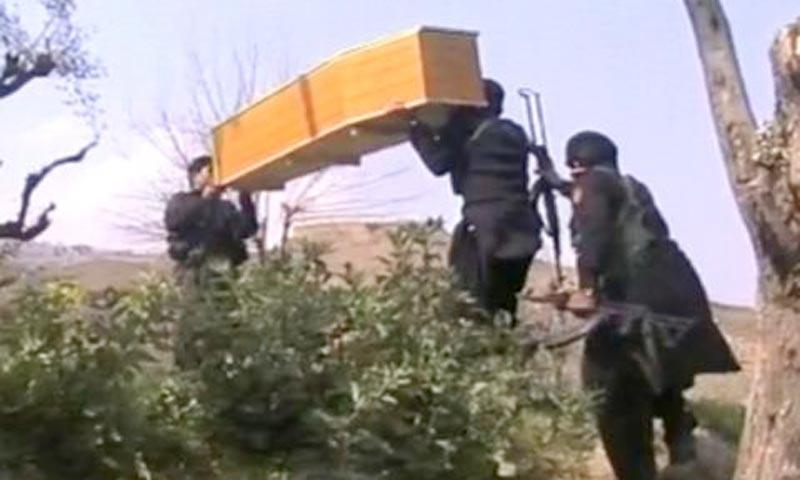 Image taken from television footage shows security carrying the coffin of one of the Khasadar personnel killed in Saturday's attack on a polio vaccination team in Jamrud, Khyber agency.—Photo by Zahir Shah Sherazi