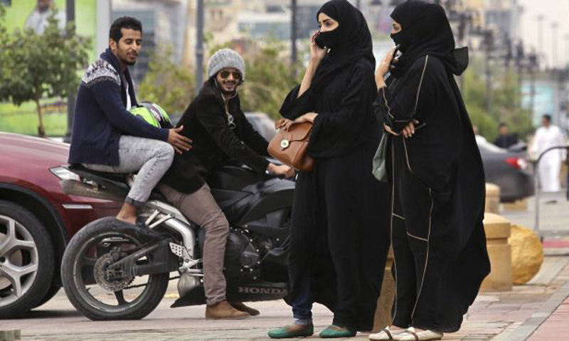 A woman speaks on the phone as men ride a motorcycle on a cloudy day in Riyadh. – File Photo by Reuters