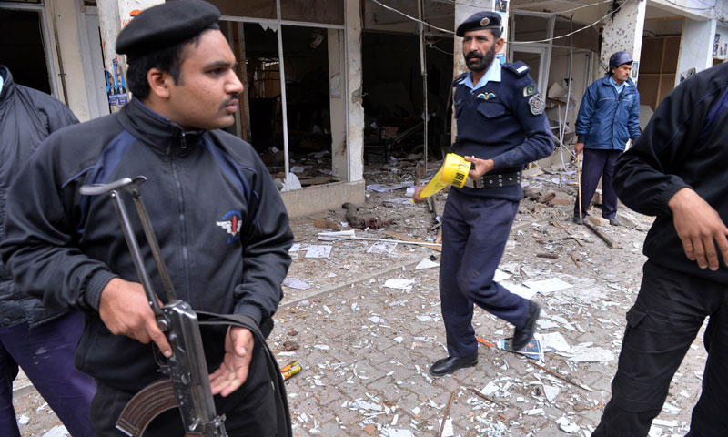 Policemen inspect a local court building after a gun and bomb attack in Islamabad, March 3. — AFP