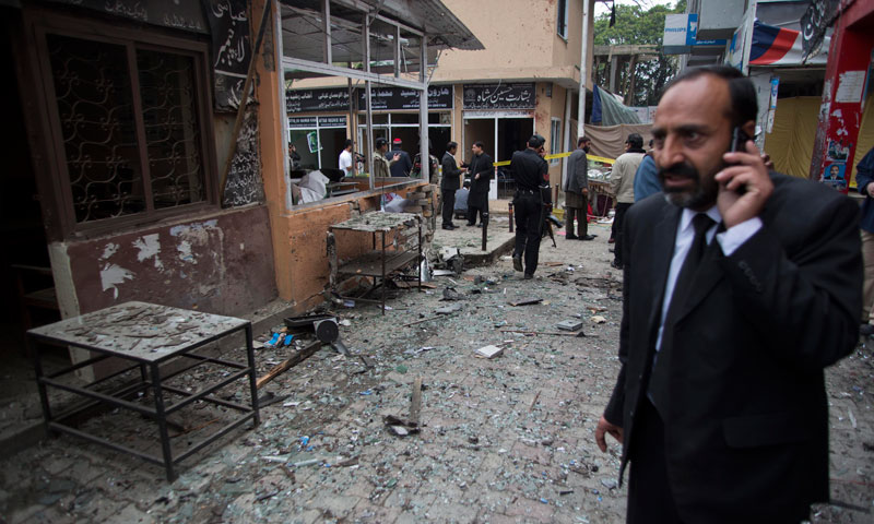 A lawyer talks on his mobile phone at the site of a bomb attack in a court complex in Islamabad, March 3. — AP