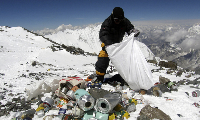 This picture taken on May 23, 2010 shows a Nepalese sherpa collecting garbage, left by climbers, at an altitude of 8,000 metres during the Everest clean-up expedition at Mount Everest.  Climbers scaling Mount Everest will have to bring back eight kilograms (17.6 pounds) of garbage under new rules designed to clean up the world's highest peak, a Nepalese official said March 3, 2014.  — File Photo