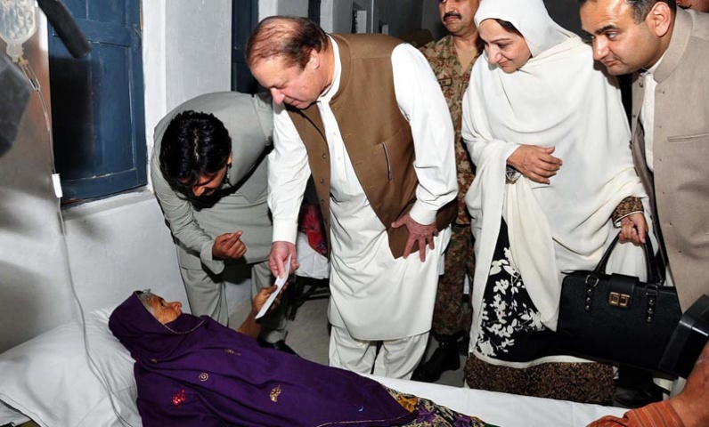 Prime Minister Nawaz Sharif giving away relief amount to an victim of Drought in Civil hospital Mitthi, district Tharparkar . — Photo by Online