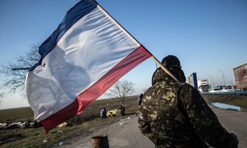 A pro-Russia supporter waves a Crimean flag at Chongar checkpoint blocking the entrance to Crimea, March 10. — Photo by AFP
