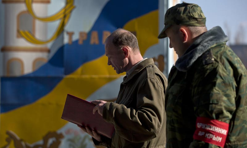 An officer, right, stands next to a civilian reading an oath during a swearing in ceremony before  joining the newly formed army of Crimea at a military base in Simferopol, Ukraine. -AP Photo
