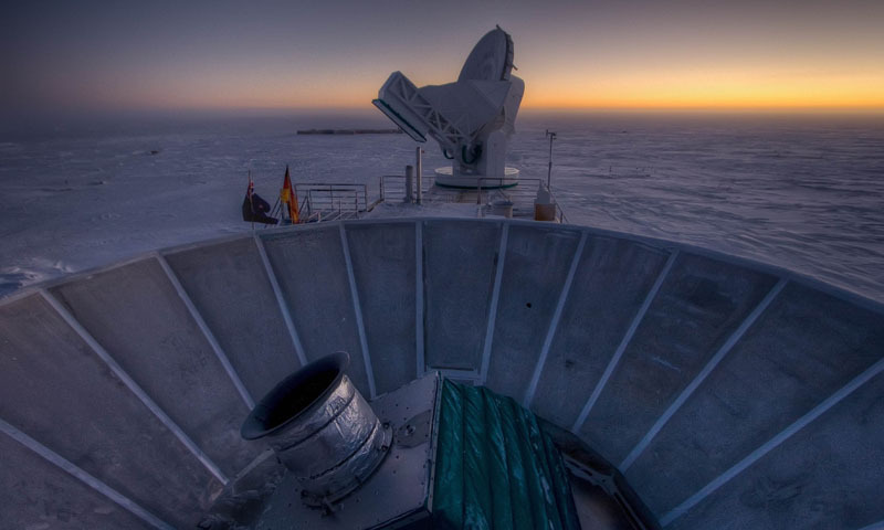 This undated handout photo courtesy of Steffen Richter shows the sun as it sets behind BICEP2 (in the foreground) and the South Pole Telescope (in the background). — AFP Photo